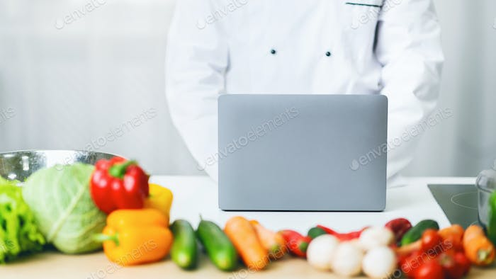 Unrecognizable Chef Man Using Laptop Writing Article In Kitchen, Panorama