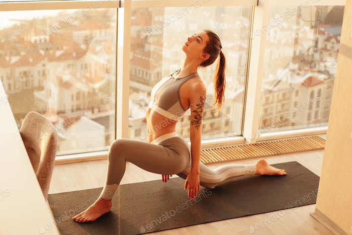 Beautiful lady in sport top and leggings practicing yoga on yoga mat at home with amazing city view