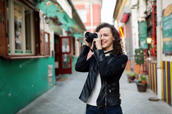 Young cute woman taking photos on street