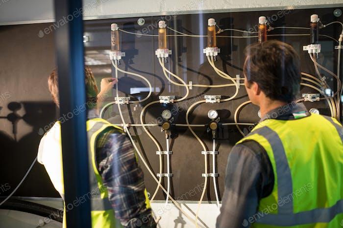 Workers examining pressure gauge
