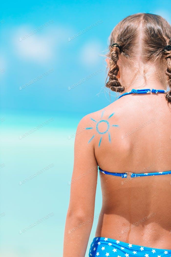 Sol de cerca pintado por crema solar en el hombro del niño
