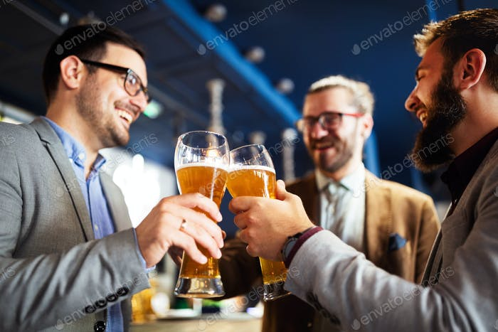 Happy young businessmen drinking beer and talking at pub after work
