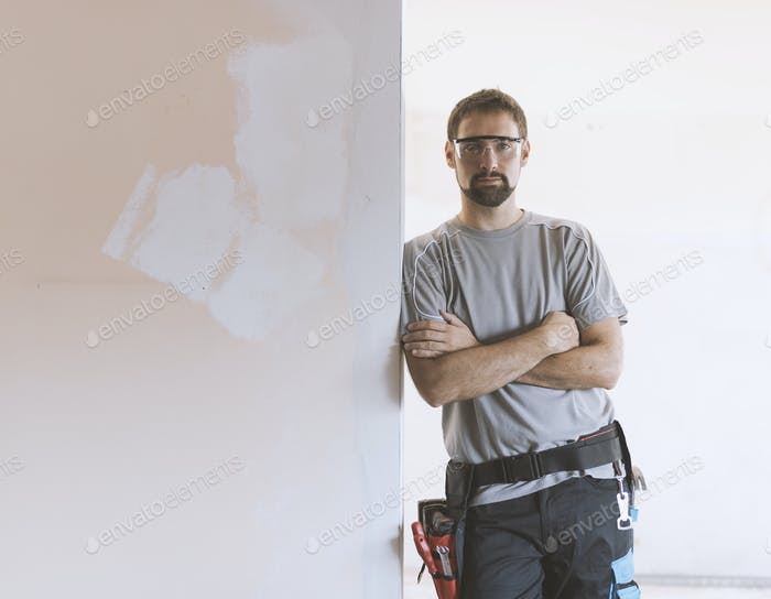Professional repairman posing and apartment under renovation