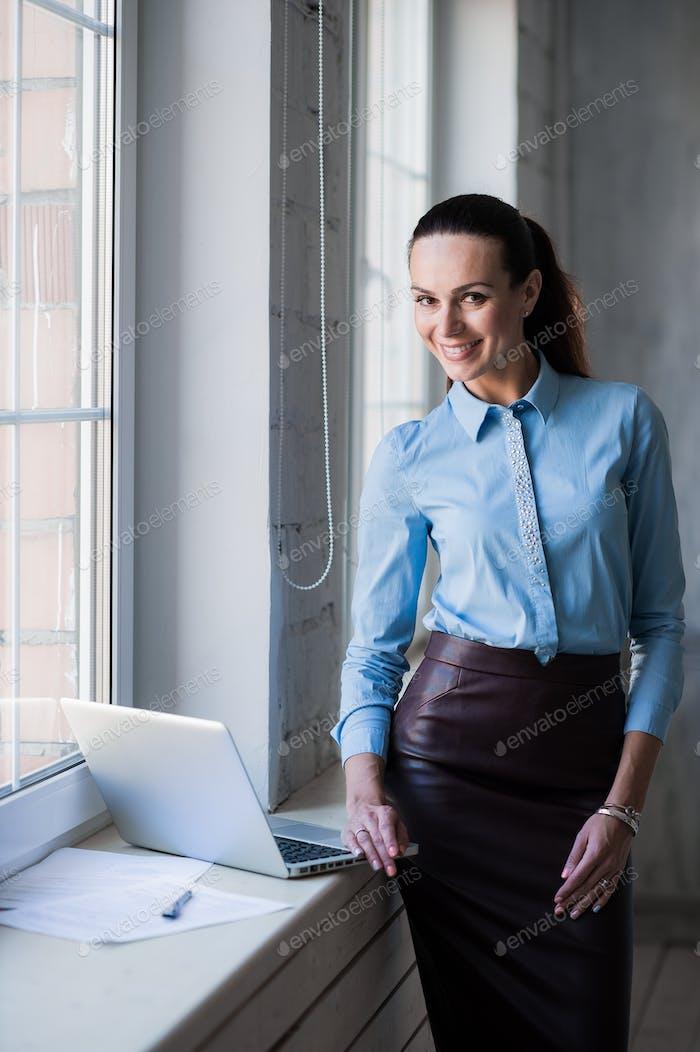 Junge erfolgreiche glückliche lächelnde Geschäftsfrau auf Laptop