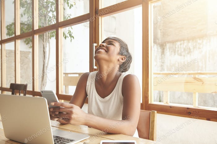 African student girl laughing out loud using smartphone, chatting with her friends online, having fu