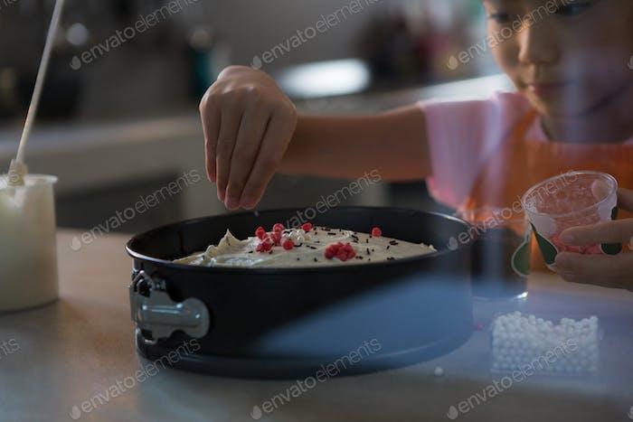 Girl decorating cake in kitchen
