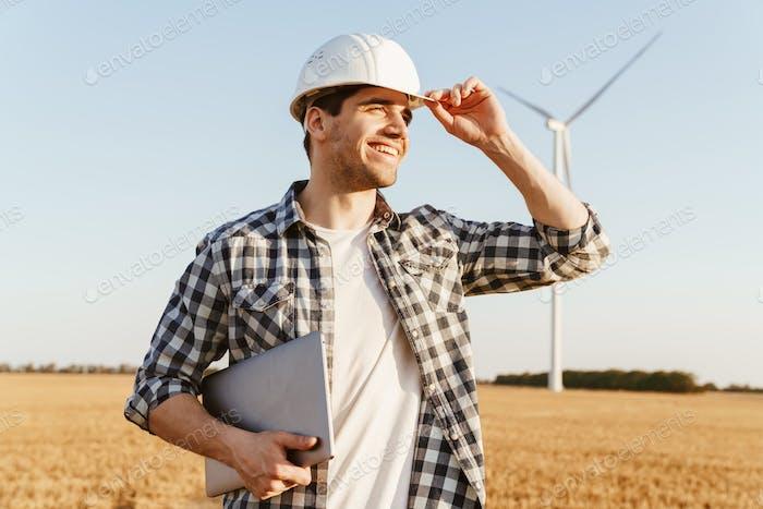 Ein Elektroingenieur, der auf einem Feld steht