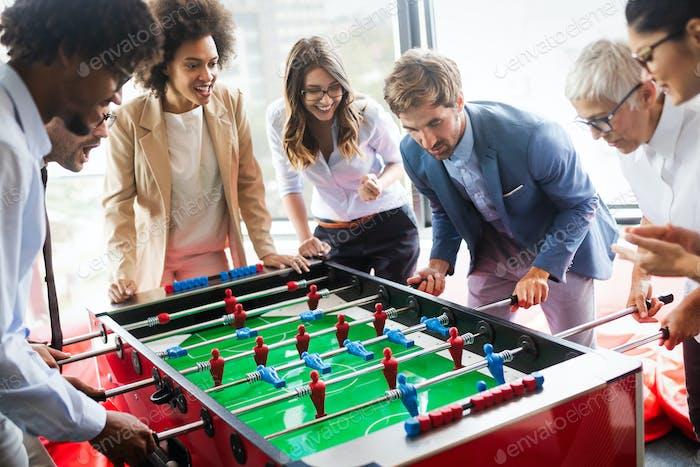 Mitarbeiter spielen Tischfußball Indoor-Spiel im Büro während der Pausenzeit