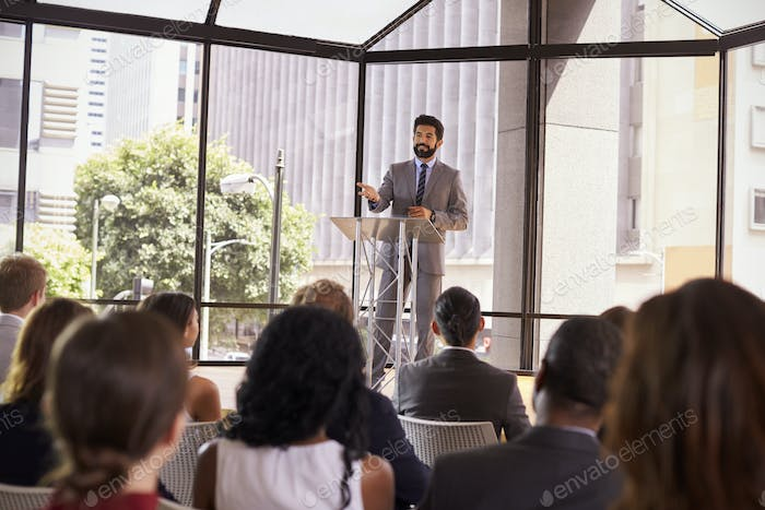Hispanic man presenting business seminar to audience