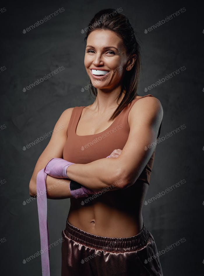 Smiling sportswoman poses in dark background with bandages