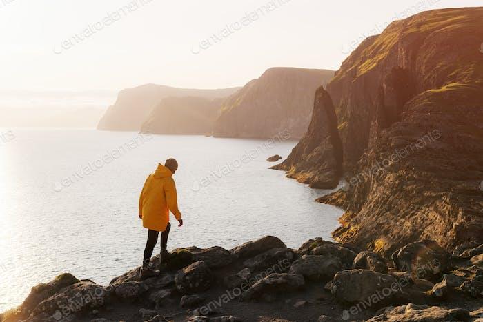 Tourist in gelber Jacke schaut auf Klippen in der Nähe von Sorvagsvatn See