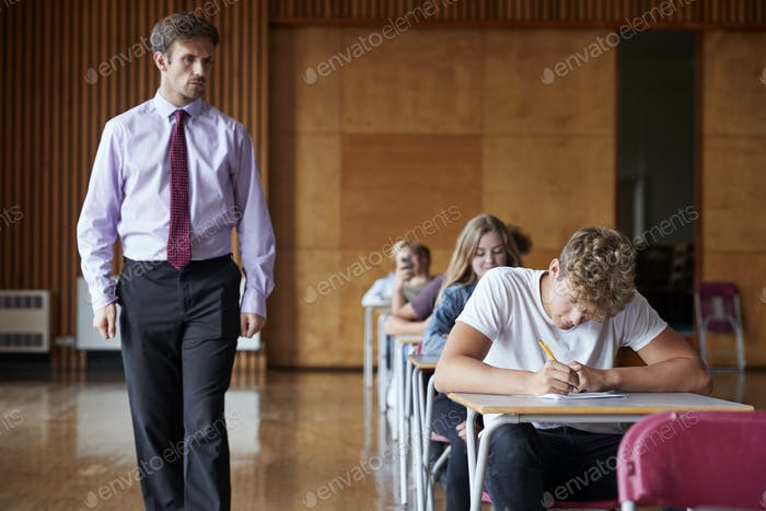 Teenage Students Sitting Examination With Teacher Invigilating