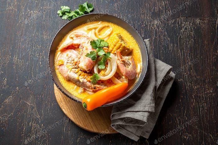 Peruvian seafood soup Chupe de Camarones in gray bowl, top view