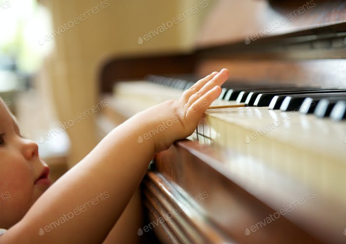 Portrait of a baby playing the piano