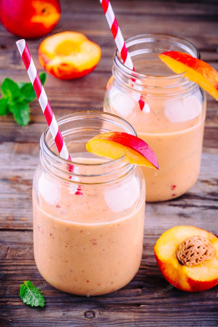 Healthy peach smoothies in a mason jar with mint on wooden background