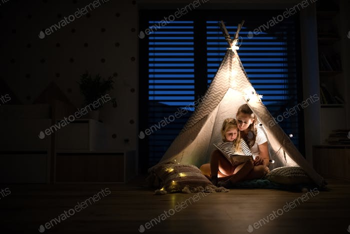 Young mother with daughter sitting indoors in bedroom, reading a book
