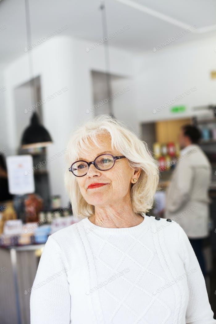 Close-up of senior woman smiling at restaurant
