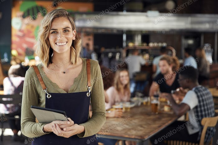 Portrait Of Waitress Holding Menus Serving In Busy Bar