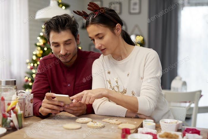Couple with mobile phone in the kitchen