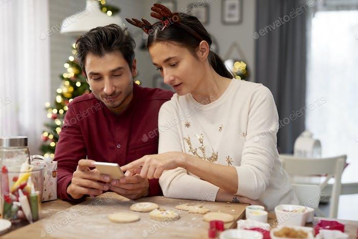 Paar mit Handy in der Küche