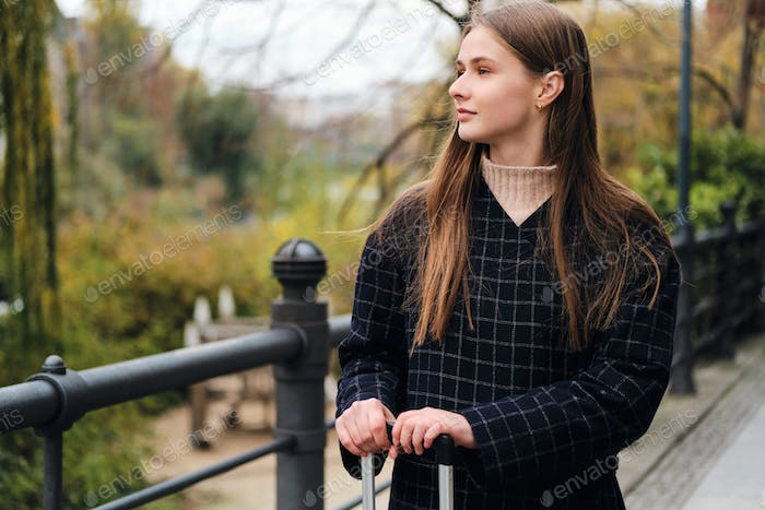 Side view of attractive casual girl in coat dreamily looking away outdoor