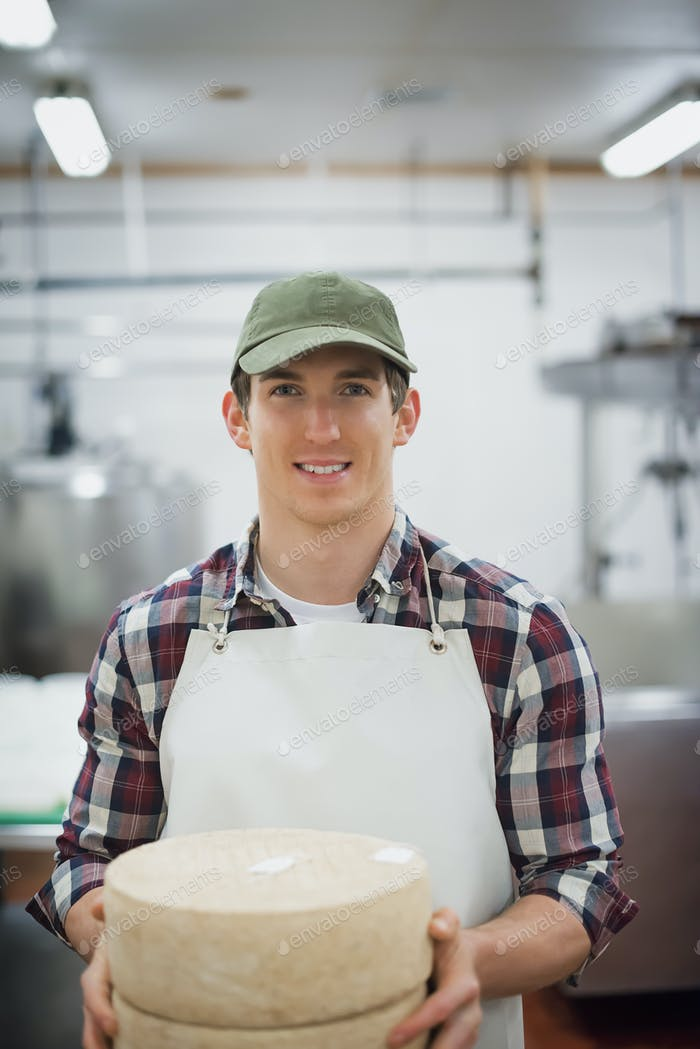 A man in a dairy building holding large wheels of cheese.
