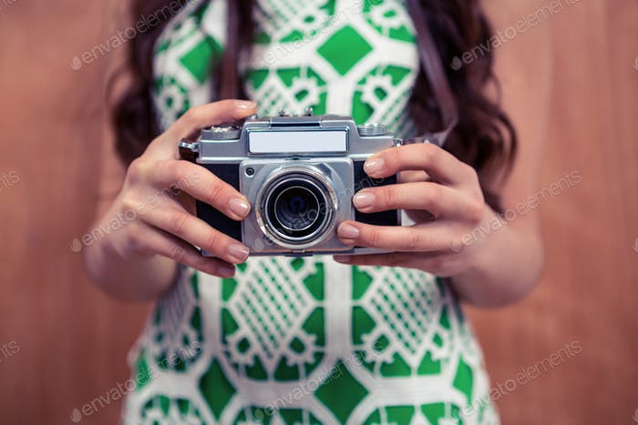 Midsection of woman holding camera against wooden wall