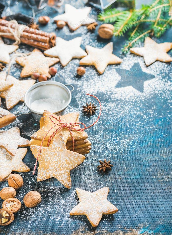 Sternförmige Kekse mit Gewürzen, Zuckerpulver und Tannenzweig