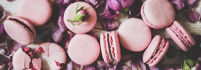 Sweet macaron cookies and rose buds and petals, wide composition