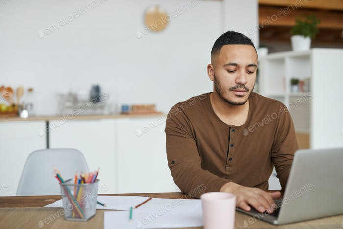 Handsome Mixed-Race Man Using Laptop at Home