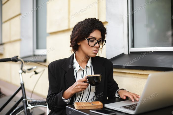 African American girl in glasses sitting at the table of cafe with cup of coffee in hands