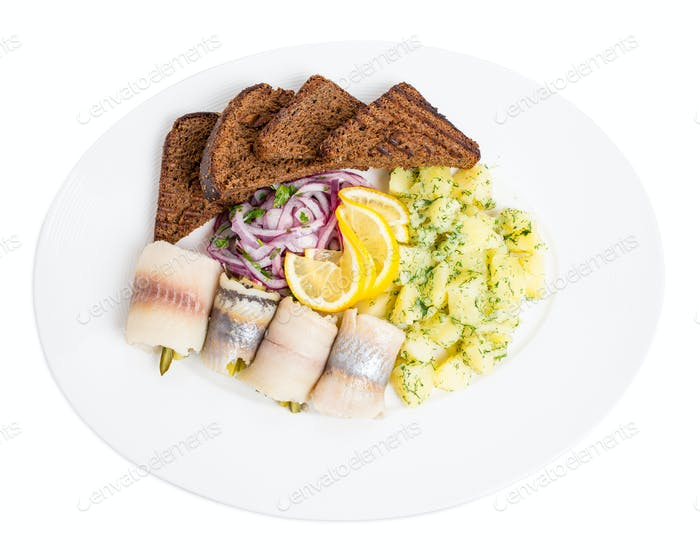 Salted herring fillet with pickles and potatoes.