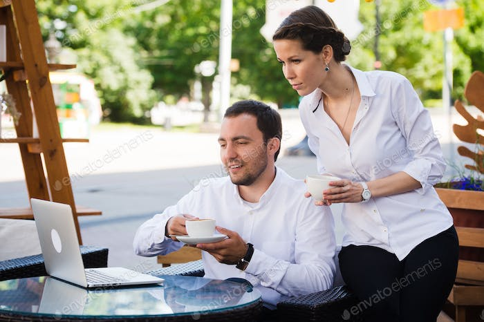 Business colleagues with a laptop working in outdoors cafe using conference internet call