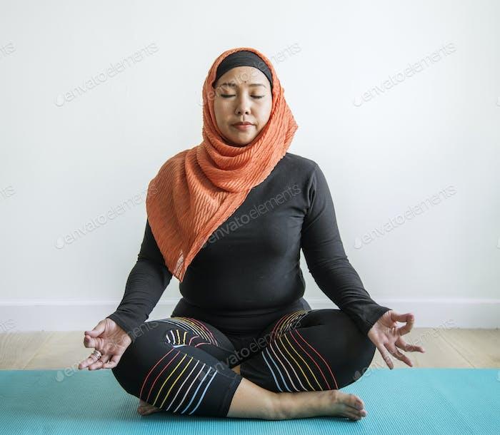 Islamic woman doing yoga in the room