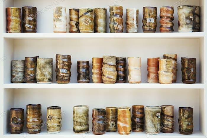 ceramic jars arranged on white shelves.