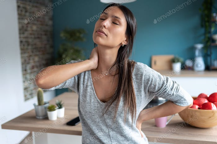 Tired young woman suffering neck pain while sitting on the stool in the kitchen at home.
