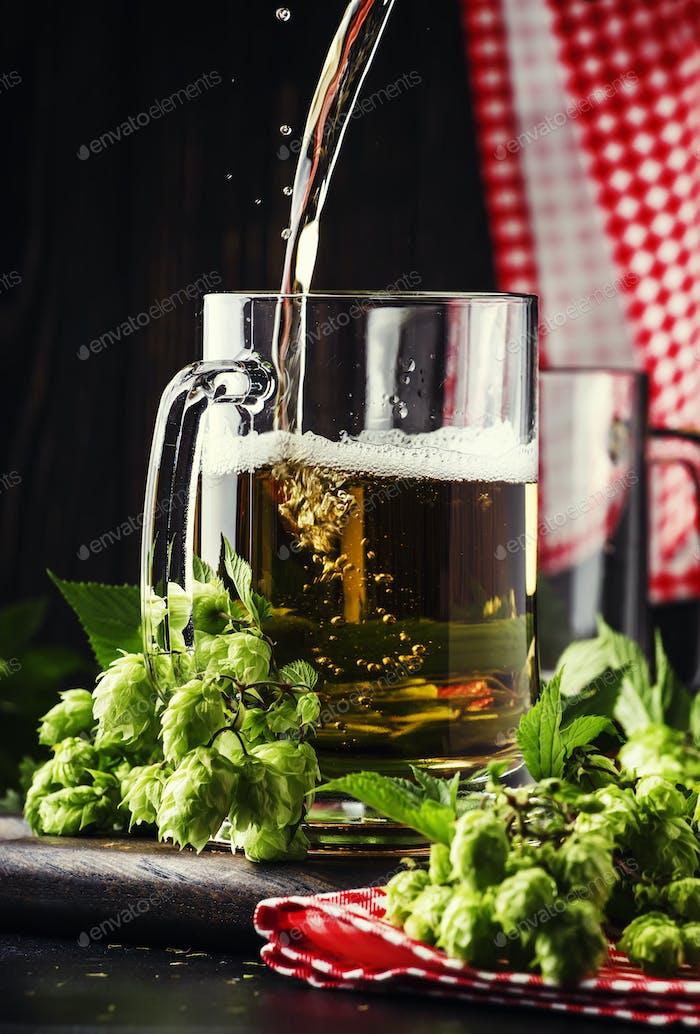 Große Tassen mit deutsches helles Bier und frischem Hopfen, gießt in Glas, dunkler Tisch