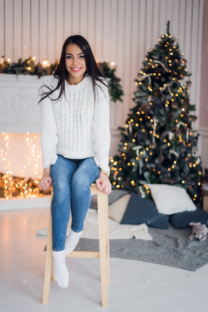 Merry Christmas celebration. Beautiful amazing young woman in a blue jeans and white sweather