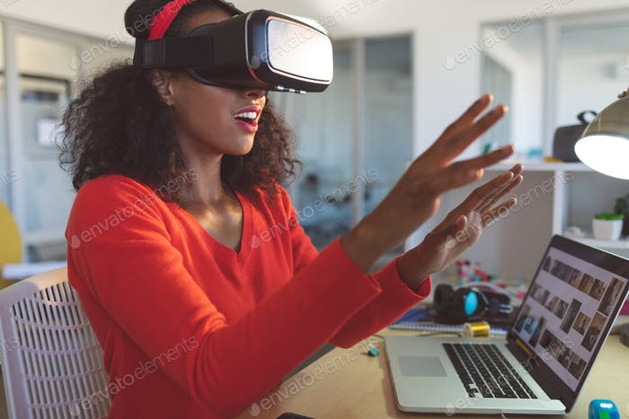 Female graphic designer using virtual reality headset at desk in a modern office