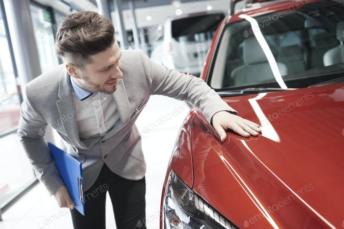 Car salesman examining vehicle before selling