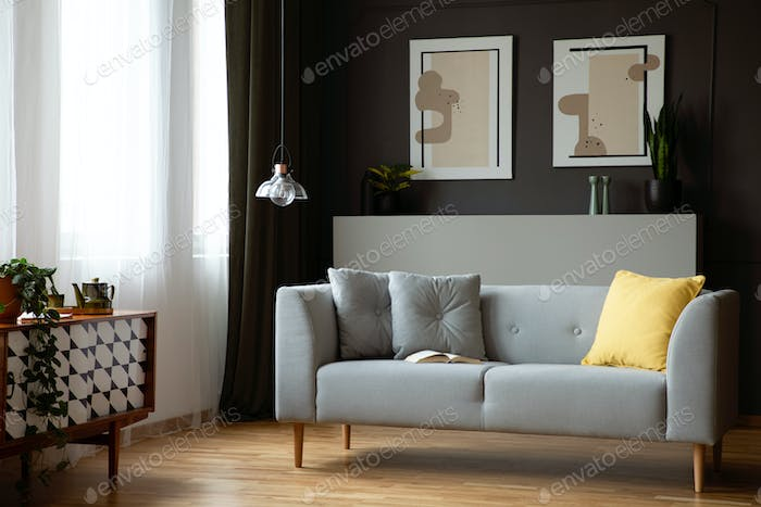 Grey lounge with yellow cushion in real photo of dark living roo