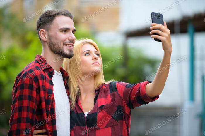 Young couple using phone together in the streets outdoors