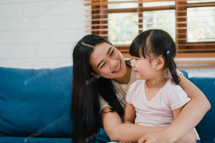 Asian family mom and daughter embracing kissing on cheek congratulating with birthday at house.