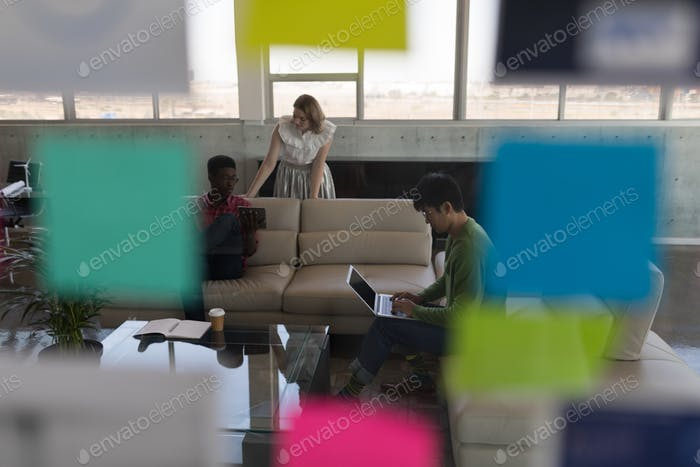 Diverse executives discussing business plans over digital tablet and laptop in office