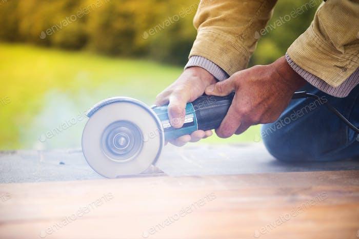 Carpenter grinding wooden planks