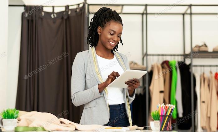 Afro Fashion Designer Using Tablet Browsing Internet In Dressmaking Studio