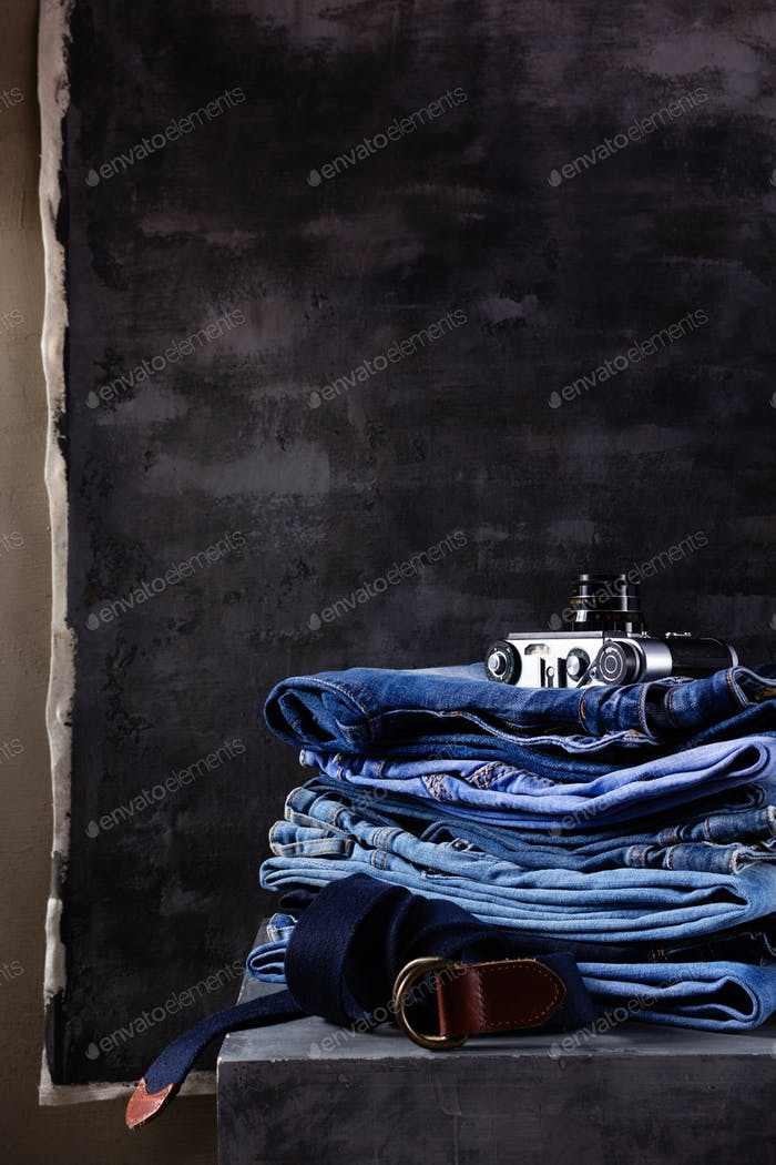 Denim jeans and leather belt at old grey cube near grey wall background.  Stack of jeans