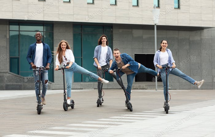 Friends having fun riding motorized kick scooters