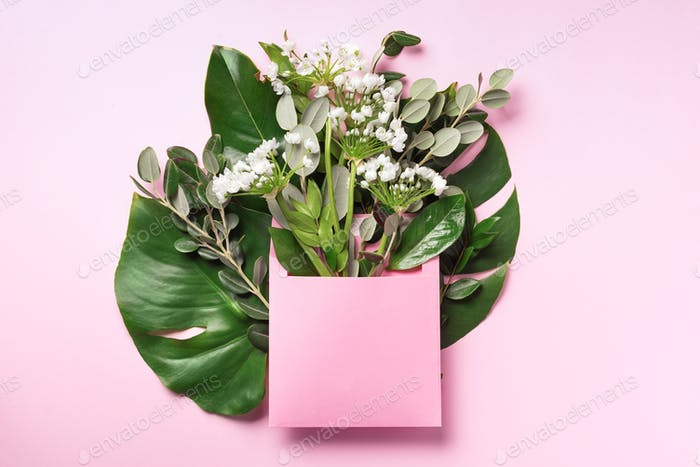 Pink envelope with spring flowers. Floral composition, creative layout. Flat lay, top view. Spring