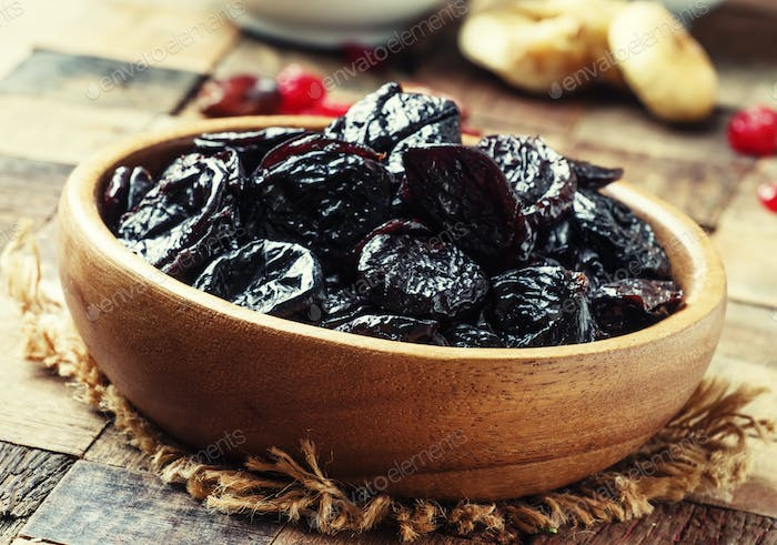 Prunes in wooden bowl